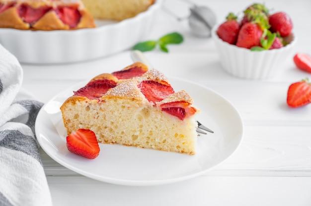新鮮なイチゴと白い木製の背景にイチゴのスポンジケーキまたはパイ