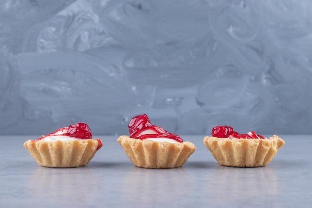 大理石の上にイチゴシロップをのせたカップケーキが並んでいます
