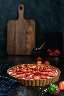 Strawberry tart on dark wooden table
