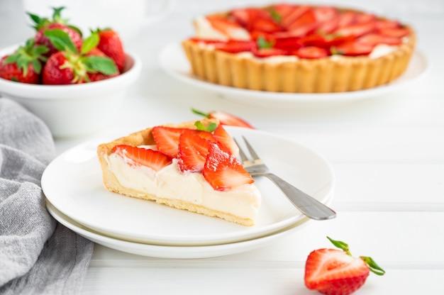 Клубничный пирог с заварным кремом на тарелке на белом деревянном фоне. скопируйте пространство.