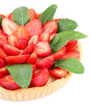 Strawberry tart with green mint leaves isolated on white