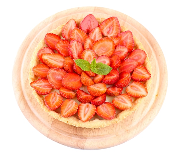 Strawberry tart with green mint leaves isolated