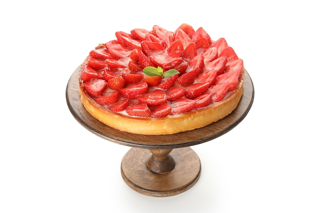 Strawberry tart on wooden stand isolated on white background.
