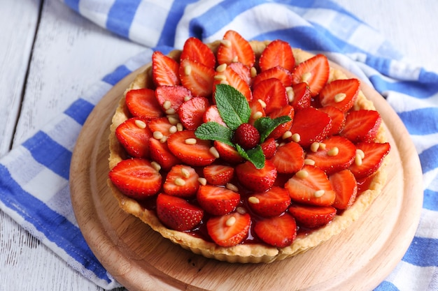 Strawberry tart on wooden tray, on color wooden background