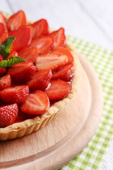 Strawberry tart on wooden tray on color wooden background