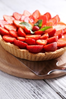 Strawberry tart on wooden tray, on color wooden table