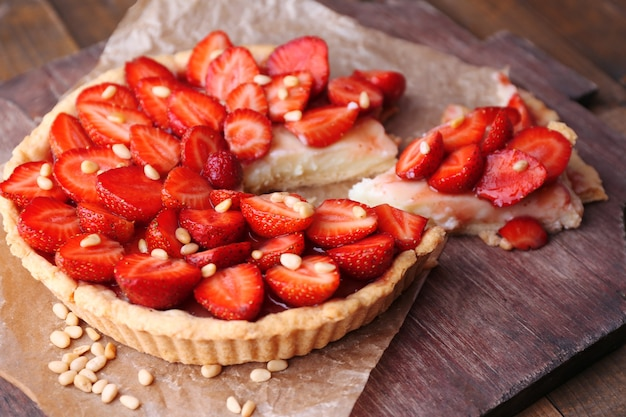 Strawberry tart on wooden tray, on rustic wooden background