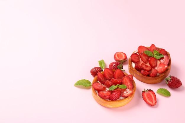 ピンクの背景、テキスト用のスペースにイチゴのタルト。