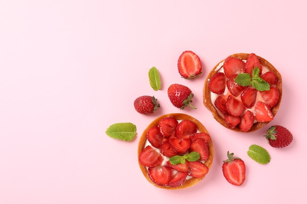 Strawberry tarts on pink background, space for text.