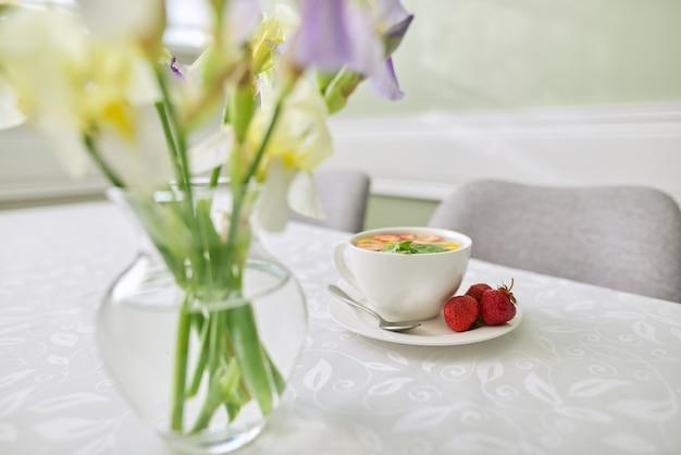 テーブルのクローズアップにミントレモンベリーとストロベリーティー。菖蒲の花瓶と窓の近くのテーブル