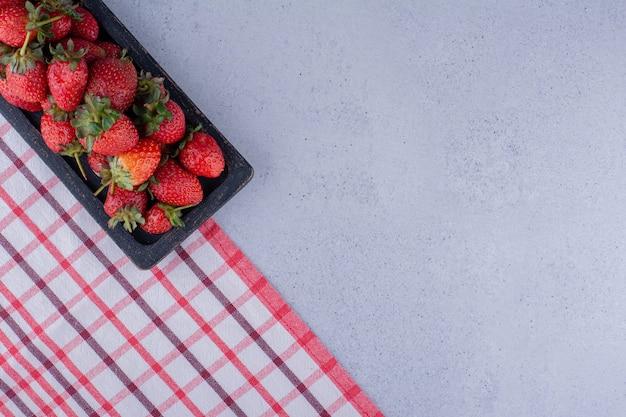 大理石の背景にテーブルクロスの端に並んだイチゴのトレイ。高品質の写真