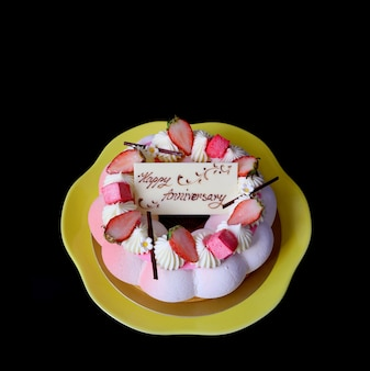 Strawberry vanilla mousse cake with edible white chocolate greeting card isolated on black background