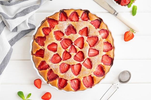新鮮なイチゴと白い木製の背景にイチゴバニラスポンジケーキまたはパイ