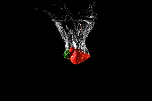 Strawberry in water with black background