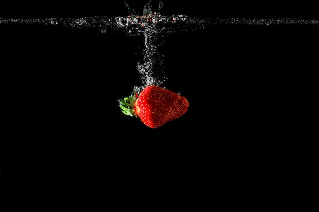 Strawberry in water with black background.