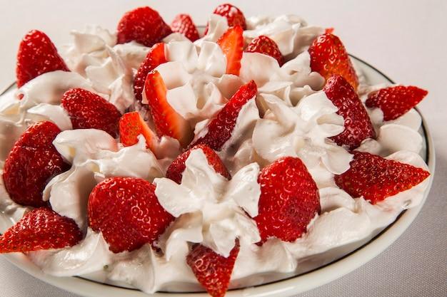 나무 테이블에 접시에 샹 티이 크림 딸기