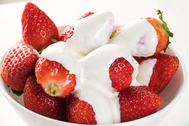흰색 테이블에 흰 그릇에 샹 티 이와 딸기 프리미엄 사진