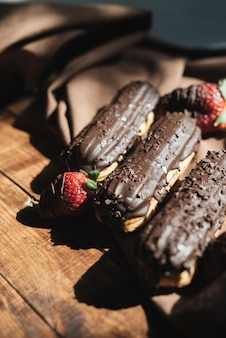 Strawberry with chocolate eclairs on wooden desk in sunlight