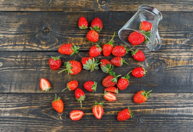 Strawberry with cup on wooden surface