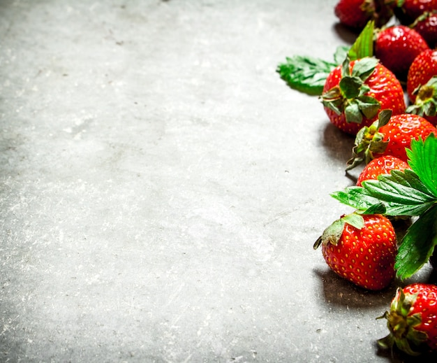 Strawberry with green leaves. on the stone table.