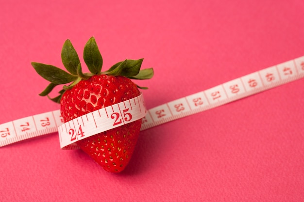 분홍색 배경에 측정 테이프와 딸기