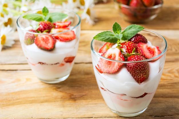 Strawberry with yogurt on rustic wood