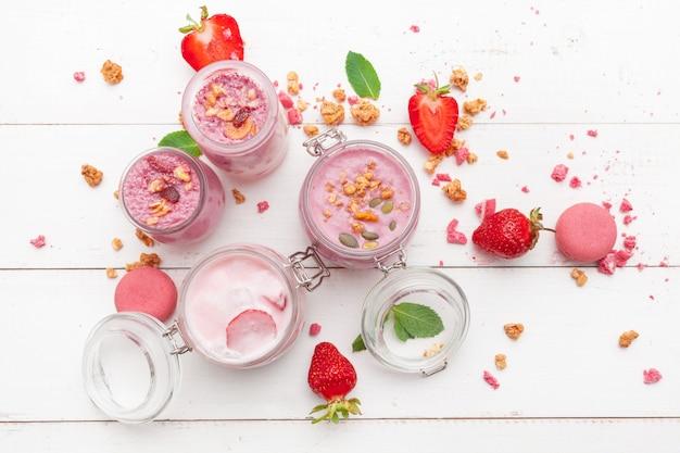 Strawberry with yogurt on white rustic wooden background. cream dessert