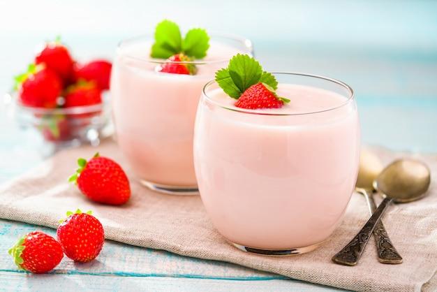 Клубничный йогурт и металлические ложки на деревянном столе