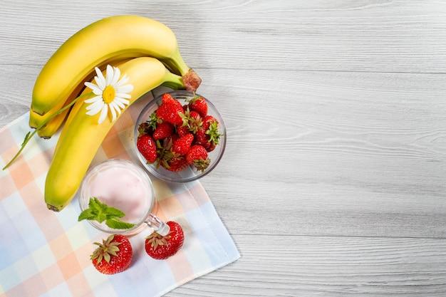 Клубничный йогурт в стакане со свежей клубникой, бананом, ромашкой на деревянном столе с салфеткой вид сверху
