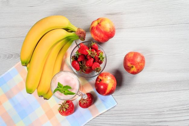 Клубничный йогурт в стакане со свежей клубникой, нектарином, бананом на деревянном столе с салфеткой вид сверху