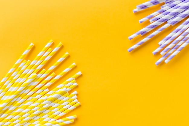 黄色の背景に分離された行のさまざまな色のstraws.environmentallyフレンドリードリンクストロー。