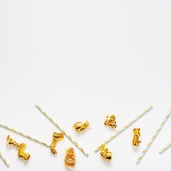 Straws and golden ribbons with copy space background