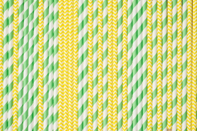 Straws in green and yellow colors background