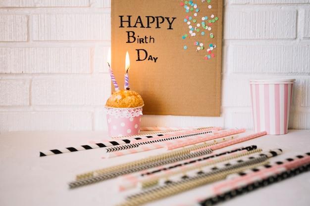 誕生日の挨拶とカップケーキの近くのストロー