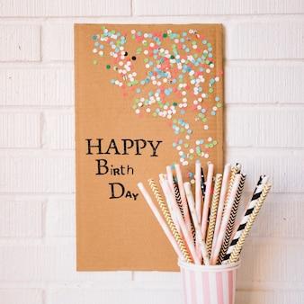 Straws near cardboard with birthday greeting