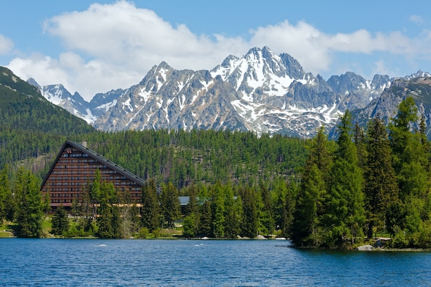 Вид на источник штрбске плесо с горным озером и отелем на берегу (словакия)