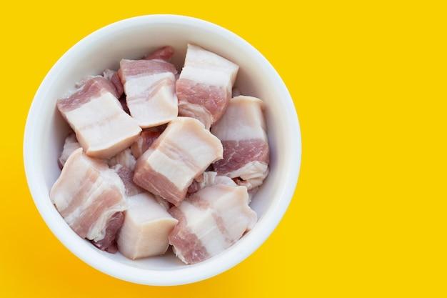 노란색 배경에 흰색 그릇에 줄무늬 돼지고기.