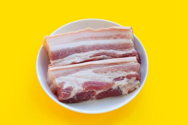 노란색 배경에 흰색 접시에 줄무늬 돼지고기입니다.
