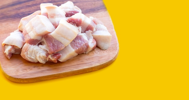 노란색 바탕에 커팅 보드에 줄무늬 돼지고기입니다.