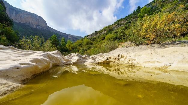 山の間の谷の侵食された岩の間を流れます。