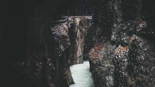 Поток течет через скалистые образования