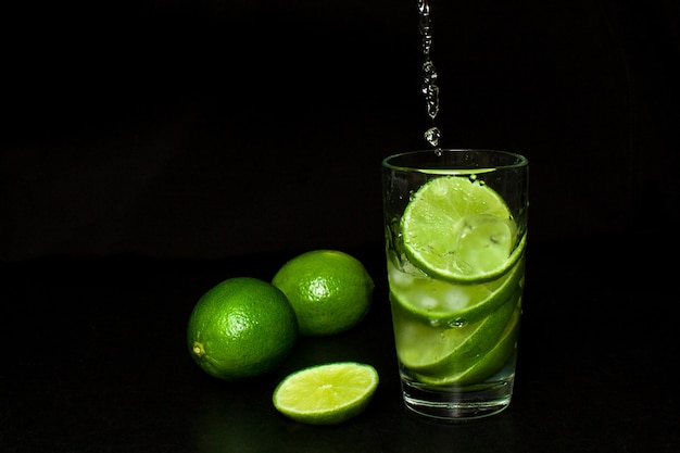 Stream pours into a glass of cold drink with ice and fresh ripe slice green limes on black