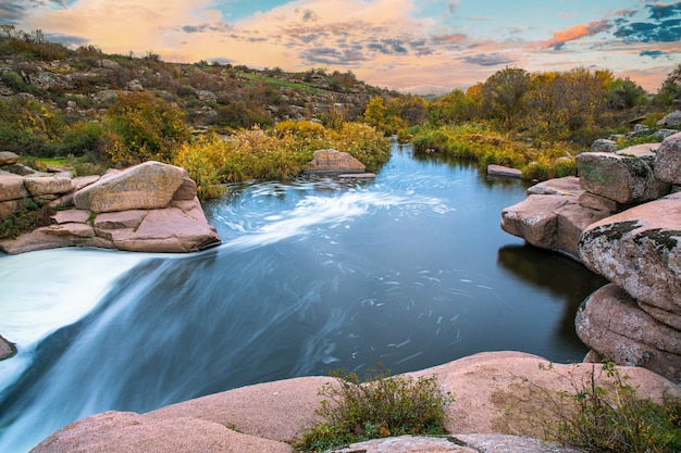 Ручей бежит среди белых мокрых камней, покрытых травой золотой осенью.