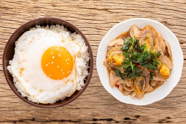 Поток риса с жареным яйцом, кунжутом сверху рядом с базиликом, обжаренным вековым яйцом, нарезанной свининой и хрустящими листьями базилика сверху на фоне текстуры натурального дерева, pad ka prao kai yeow ma, тайская кухня