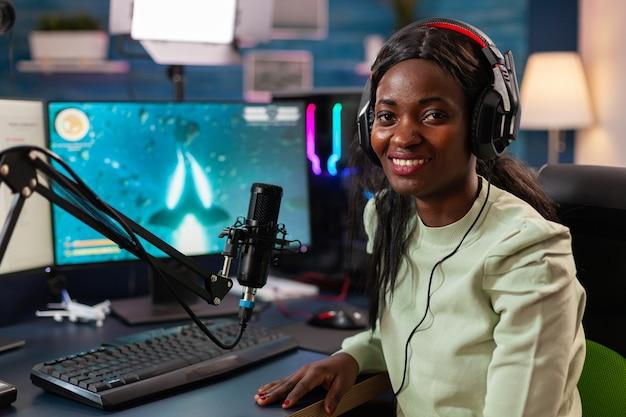 스트리머 아프리카 여성 전문 게이머가 온라인 게임 컴퓨터, rgb 색상을 하고 있습니다. 온라인 챔피언십을 위해 헤드폰과 키보드를 사용하여 재미를 위해 바이러스성 비디오 게임을 스트리밍합니다.