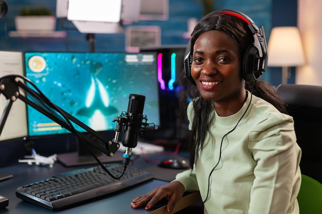 Streamer african woman professional gamer playing online games computer, rgb color. streaming viral video games for fun using headphones and keyboard for online championship.
