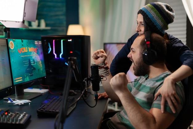 プロのヘッドセット、マイク、キーパッドを使用してオンラインスペースシューティングゲームで優勝したストリーマーカップル。強力なコンピューターで新しいグラフィックを使用してオンラインビデオゲームをプレイするゲーマー