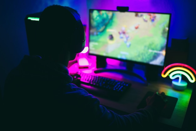 Стример-геймер, играющий в стратегическую онлайн-игру - сосредоточьтесь на наушниках