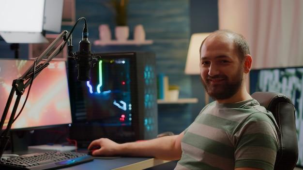 Streamer uomo che guarda la telecamera sorridendo durante lo streaming di videogiochi utilizzando la chat in streaming. videogiocatore informatico professionista che gioca a un videogioco sparatutto spaziale su un potente personal computer rgb in uno studio domestico di gioco