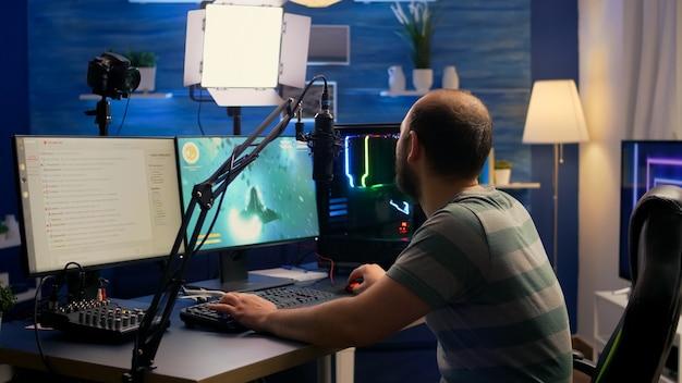 스 트리머 남자 게임 의자에 앉아 온라인 토너먼트 동안 우주 사수 비디오 게임을 시작합니다.